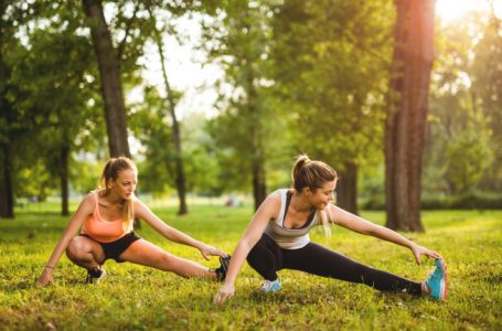 Two beautiful girls exercising together in the park.
